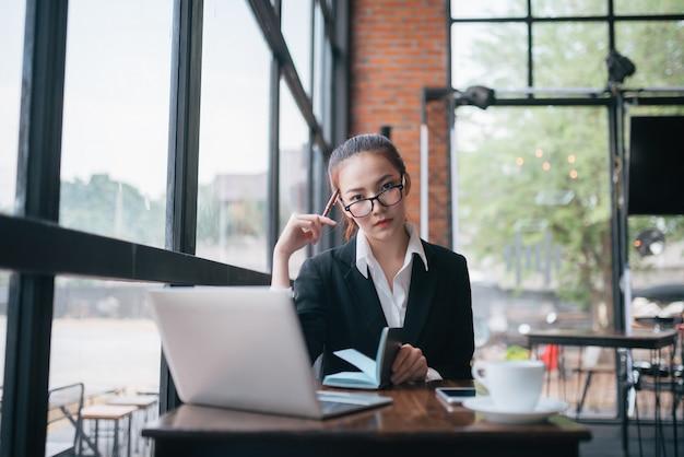 Schöne junge geschäftsfrau, die am tisch sitzt und kenntnisse nimmt. im cafe