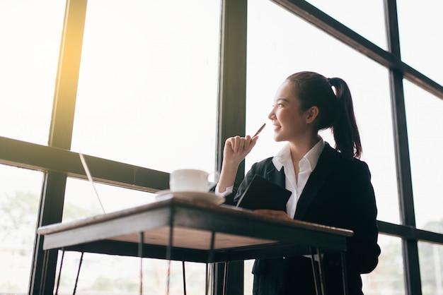 Schöne junge geschäftsfrau, die am tisch sitzt und kenntnisse nimmt