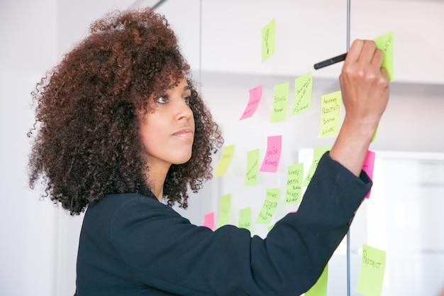 Schöne junge geschäftsfrau, die auf aufkleber mit marker schreibt. konzentrierte professionelle lockige managerin, die ideen für das projekt teilt und sich notizen macht