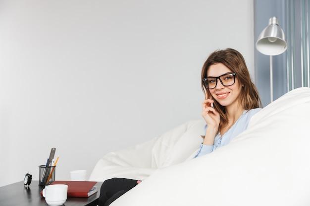 Schöne junge geschäftsfrau, die auf einer couch im büro sitzt und auf handy spricht
