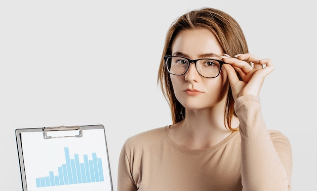 Schöne junge geschäftsfrau, die brille lokalisiert auf grauem hintergrund trägt.
