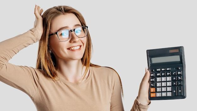 Schöne junge geschäftsfrau, die brille trägt, hält rechner lokalisiert auf graue wand. erreichen von business wealth business accounting-konzept