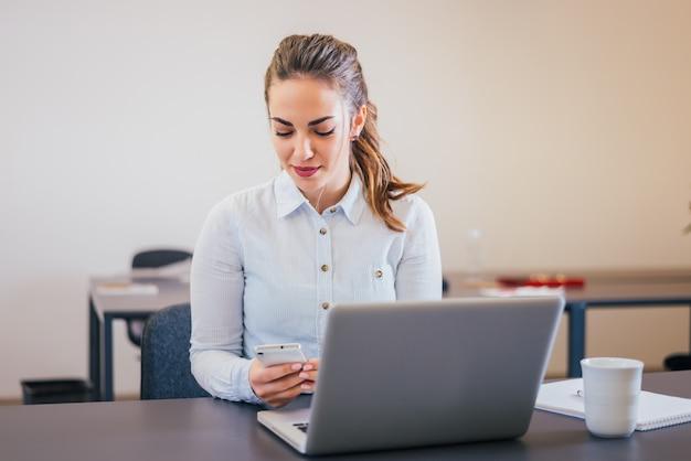 Schöne junge geschäftsfrau, die das telefon beim sitzen vor einem laptop betrachtet