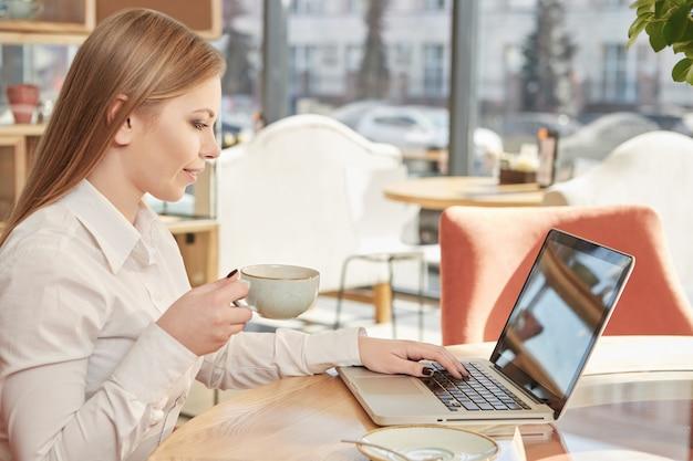 Schöne junge geschäftsfrau, die den kaffee, arbeitend an laptop am café genießt