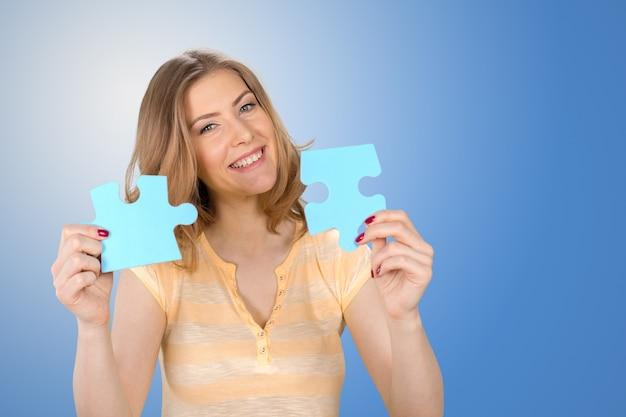 Schöne junge geschäftsfrau, die ein blaues puzzlespielstück anhält