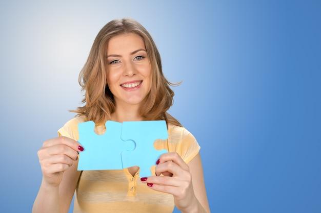 Schöne junge geschäftsfrau, die ein blaues puzzleteil hält