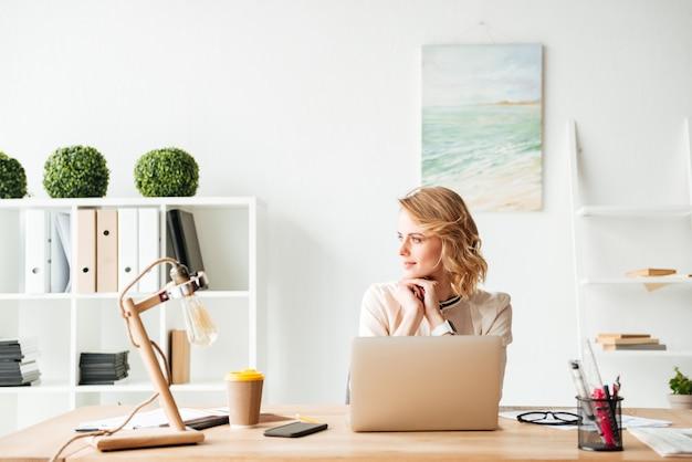 Schöne junge geschäftsfrau, die im büro sitzt