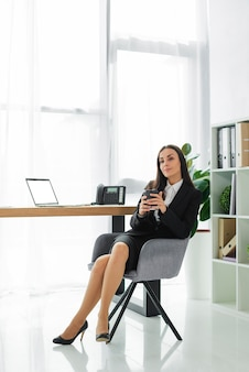 Schöne junge geschäftsfrau, die in der hand die wegwerfkaffeetasse sitzt auf stuhl hält