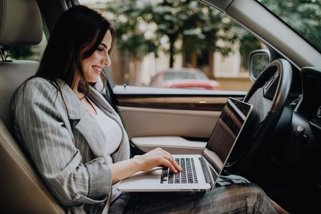 Schöne junge geschäftsfrau, die laptop und telefon im auto verwendet.