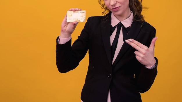 Schöne junge geschäftsfrau, die lokal über gelbem hintergrund steht und kreditkarte hält