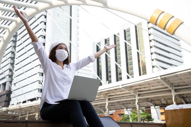 Schöne junge geschäftsfrau, die mit laptop arbeitet und hände für erfolgreiches projekt auf himmelsspaziergang mit brückenkurve im stadtbild zeigt