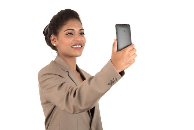 Schöne junge geschäftsfrau, die smartphone verwendet, um selfie-foto lokalisiert auf weißem hintergrund zu machen