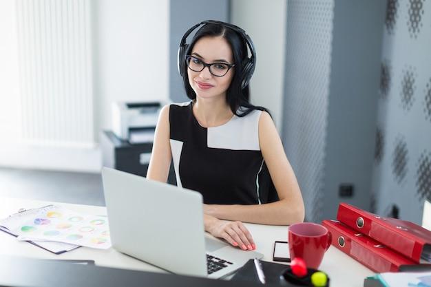 Schöne junge geschäftsfrau im schwarzen kleid, in den kopfhörern und in den gläsern sitzen am tisch und arbeiten an laptop
