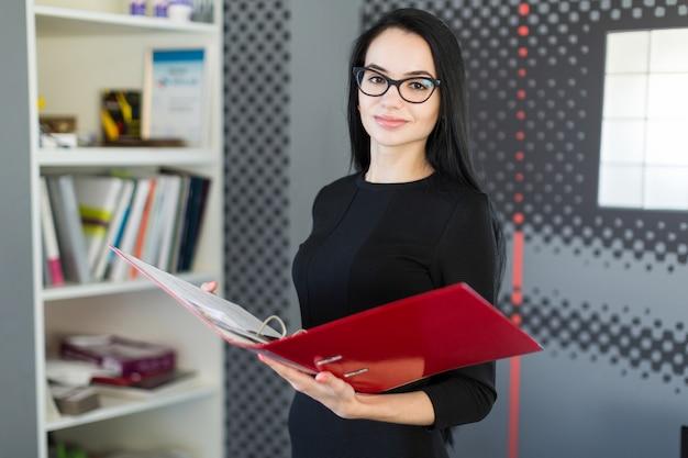 Schöne junge geschäftsfrau im schwarzen kleid und in den gläsern halten papierordner