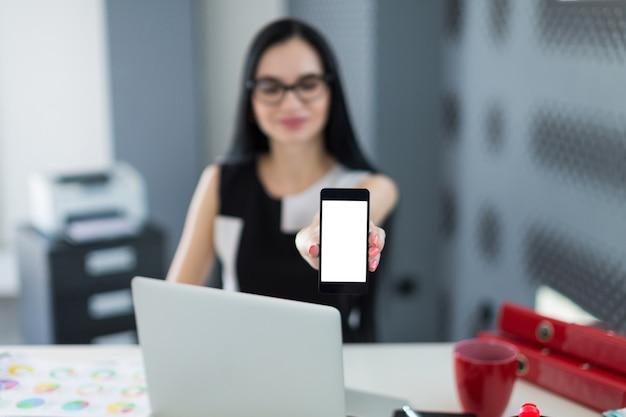 Schöne junge geschäftsfrau im schwarzen kleid und in den gläsern sitzen am tisch, arbeiten und zeigen ein telefon