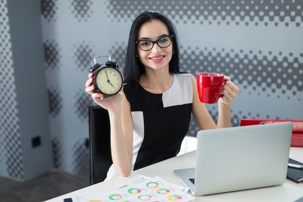 Schöne junge geschäftsfrau im schwarzen kleid und in den gläsern sitzen am tisch und arbeiten mit laptop, griffschale und wecker