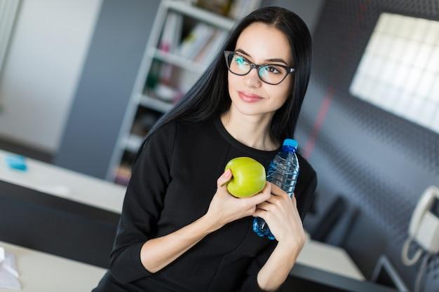 Schöne junge geschäftsfrau im schwarzen kleid und in den gläsern sitzen auf tabelle im büro und halten grünen apfel und flasche