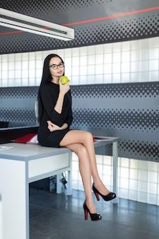 Schöne junge geschäftsfrau im schwarzen kleid und in den gläsern sitzen auf tabelle im büro und halten grünen apfel