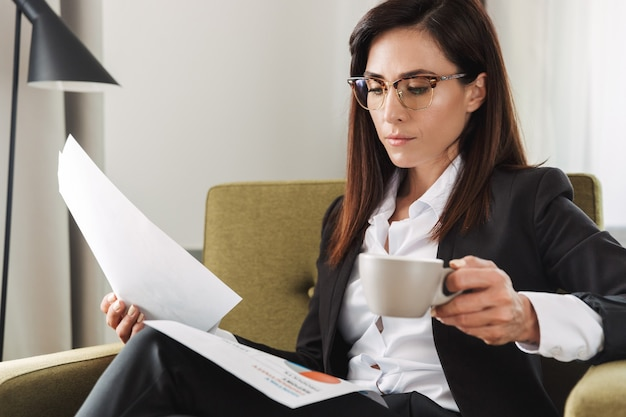 Schöne junge geschäftsfrau in formeller kleidung drinnen zu hause trinken kaffee arbeiten mit dokumenten.