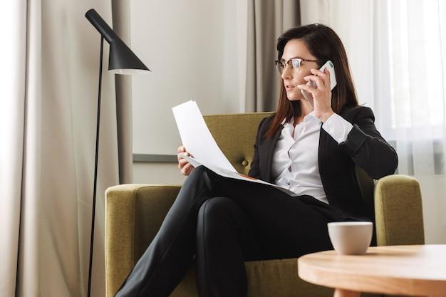Schöne junge geschäftsfrau in formeller kleidung zuhause zu hause telefonieren mit dokumenten.