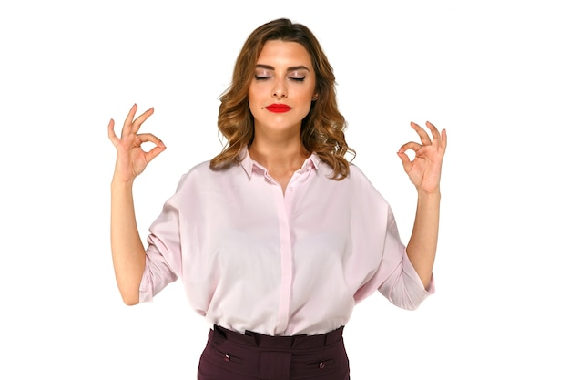 Schöne junge geschäftsfrau meditiert und versucht, sich nach der arbeit zu beruhigen