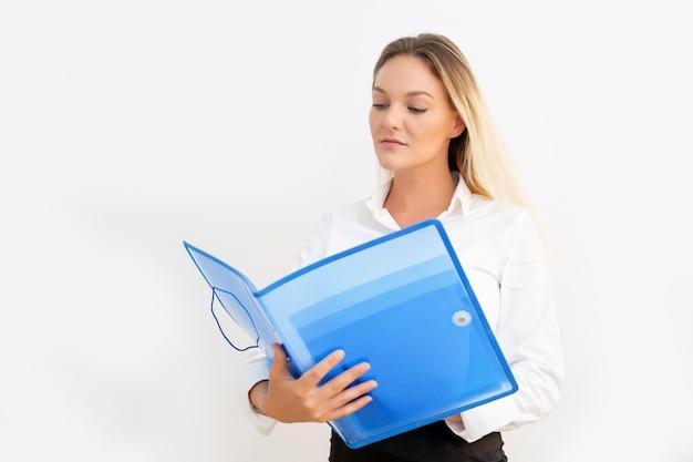 Schöne junge geschäftsfrau mit blauem ordner in den händen, mit weißer wand.