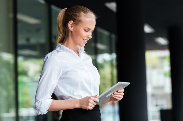 Schöne junge geschäftsfrau mit digitalem tablet beim stehen am glasgeländer im freien