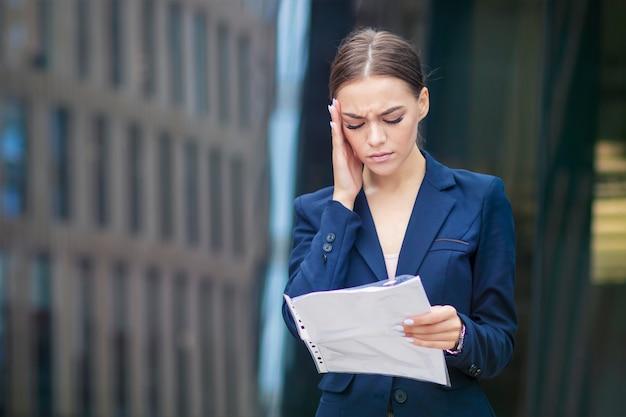 Schöne junge geschäftsfrau mit dokumenten leidet unter kopfschmerzen