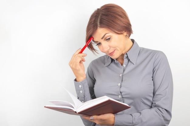 Schöne junge geschäftsfrau mit einem roten stift und einem notizbuch in den händen auf einem weiß