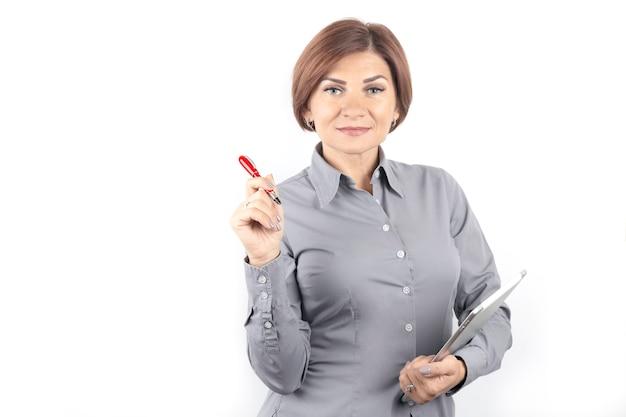 Schöne junge geschäftsfrau mit einem roten stift und einem notizbuch in den händen
