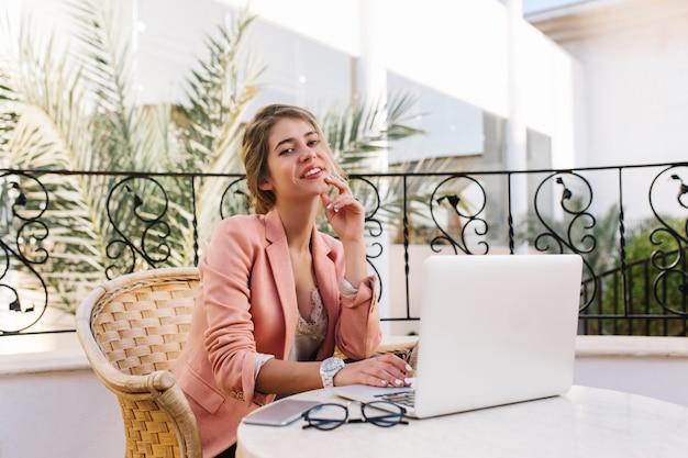 Schöne junge geschäftsfrau, student, der auf terrasse, im café sitzt, am laptop arbeitet, arbeit genießt. trägt stilvolle rosa jacke, weiße uhren. brille und smartphone auf dem tisch.