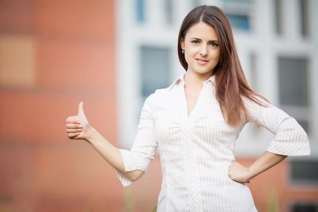 Schöne junge geschäftsfrau unter dem modernen geschäftszentrum