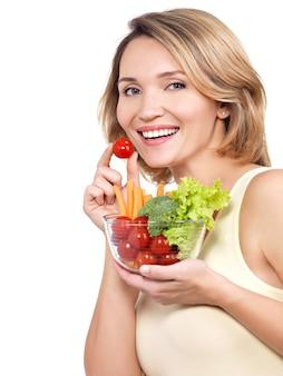 Schöne junge gesunde frau mit einer platte des gemüses lokalisiert auf weiß.
