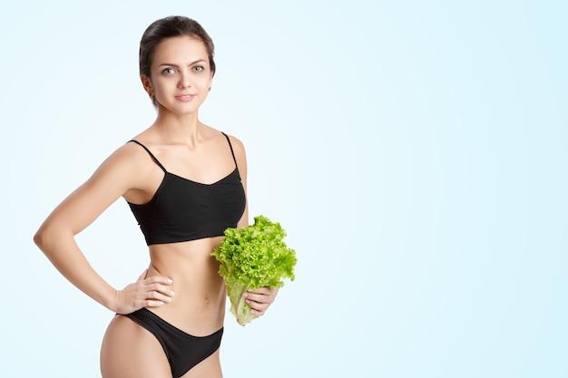 Schöne junge gesunde frau mit salatblättern. diät und gesunde ernährung