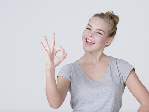Schöne junge glückliche aufgeregte frau zeigt okay zeichen auf weißem hintergrund
