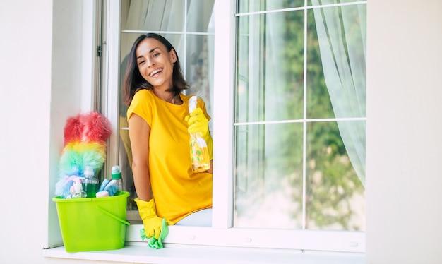 Schöne junge glückliche frau benutzt einen staubtuch und ein spray, während sie ein fenster im haus putzt