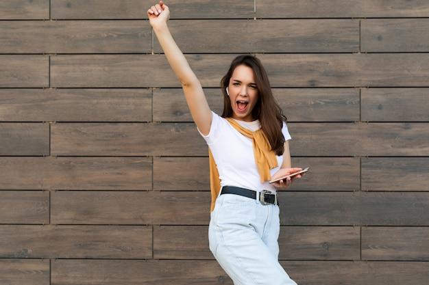 Schöne junge glückliche frau des brunet, die freizeitkleidung trägt und musik über drahtlos hört