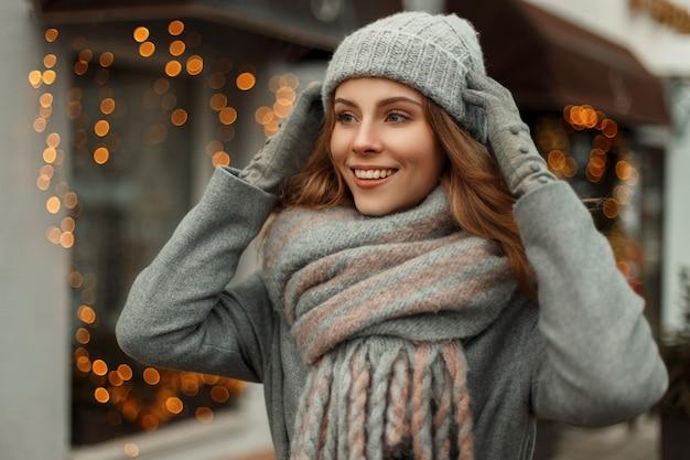 Schöne junge glückliche frau, die in einem grauen mantel mit einer trendigen strickmütze und stilvollem modeschal lächelt, der in den städten an feiertagen geht