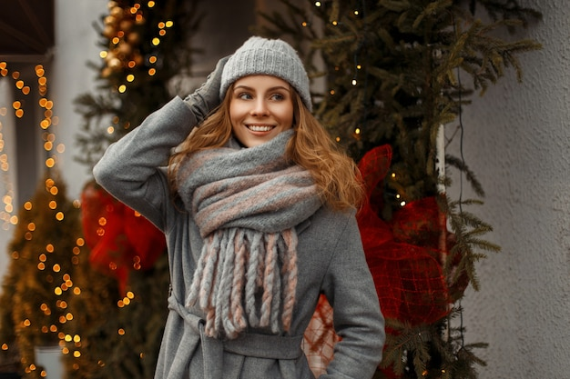 Schöne junge glückliche frau, die mit einer guten feiertagsstimmung im winter warme strickkleidung in einer mode-strickmütze und einem stilvollen schal auf der straße nahe den lichtern und girlanden lächelt