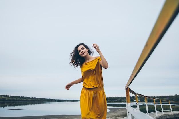 Schöne junge glückliche frau geht entlang des geländers einer konstruktion in einem hellen kleid
