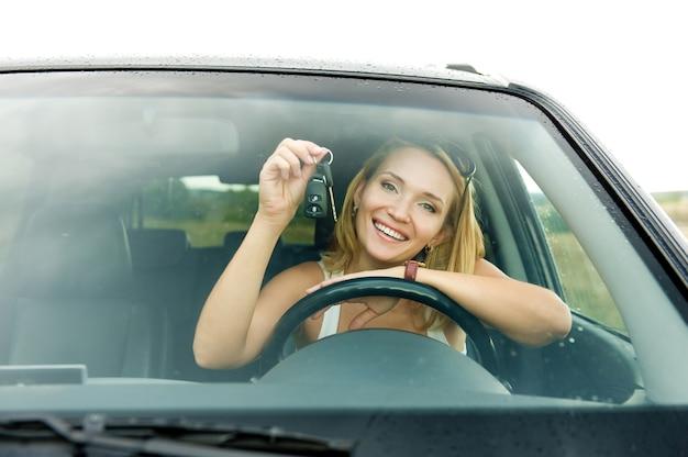 Schöne junge glückliche frau im neuen auto mit schlüsseln - draußen