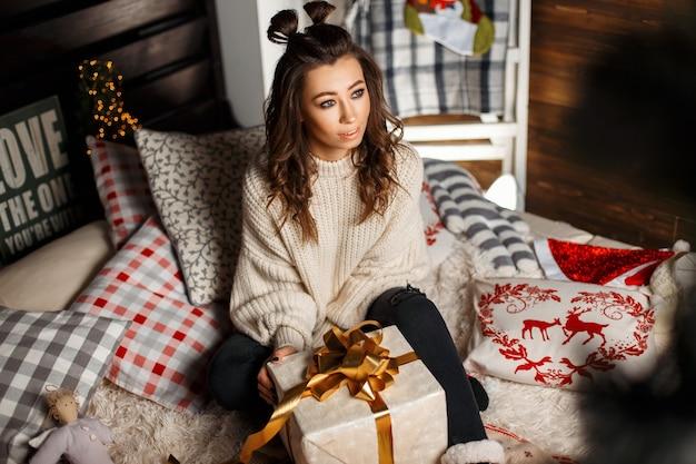 Schöne junge glückliche frau in einem stilvollen weinlesepullover mit einem geschenk auf dem bett am heiligabend. mädchen in einem gestrickten pullover mit einem geschenk mit band auf dem bett mit weihnachtsmustern