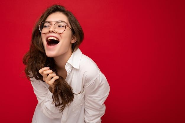 Schöne junge glückliche fröhliche lustige gelockte brunettefrau, die weißes hemd und optische brille trägt