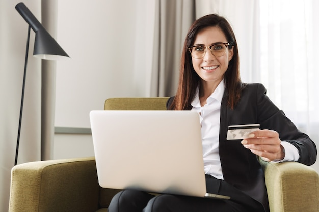 Schöne junge glückliche geschäftsfrau in formeller kleidung zuhause zu hause arbeiten mit laptop-computer, der kreditkarte hält.