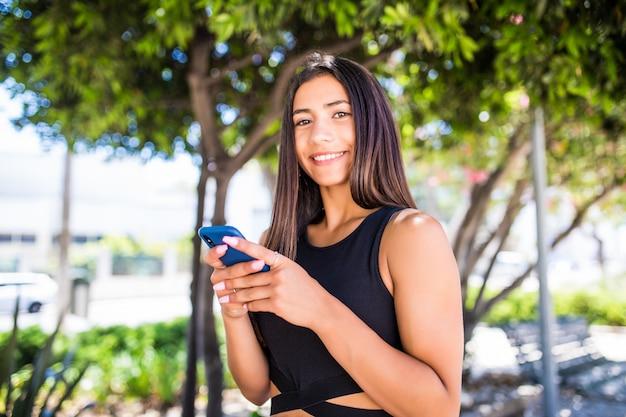 Schöne junge glückliche lateinische frau, die auf handy auf stadtstraße sms schreibt. studentin, die im winter auf der stadtstraße im freien auf dem handy geht und eine sms sendet.