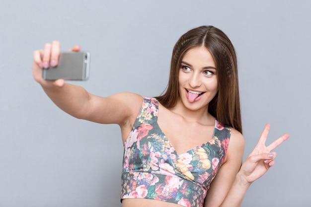 Schöne junge glückliche selbstbewusste frau in floralem top, die selfie macht und zunge zeigt