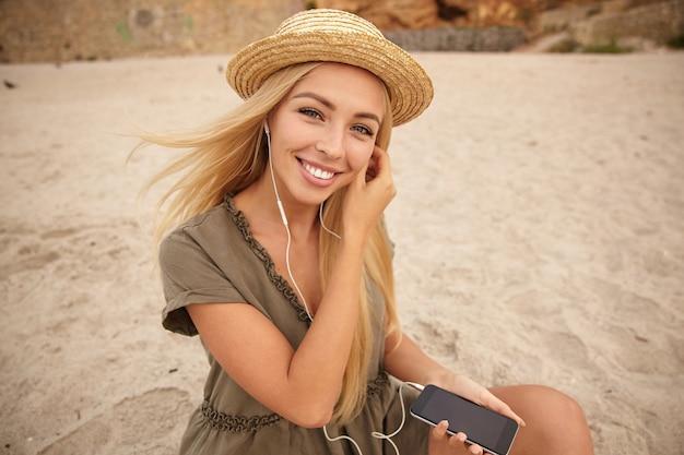 Schöne junge grünäugige blonde frau mit natürlichem make-up, das fröhlich in die kamera mit breitem lächeln schaut, während kopfhörer in ohr einfügt, über strandhintergrund sitzend