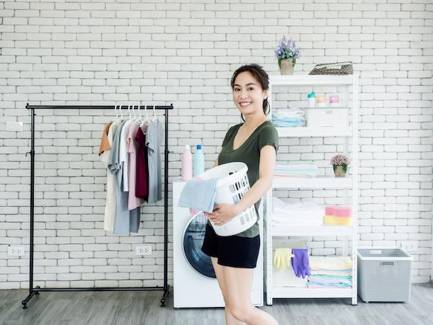 Schöne junge hausfrau der asiatischen frau, die weißen stoffkorb mit dem lächeln nahe der waschmaschine im waschraum steht und hält.