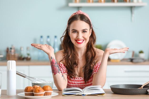 Schöne junge hausfrau, die in der küche kocht