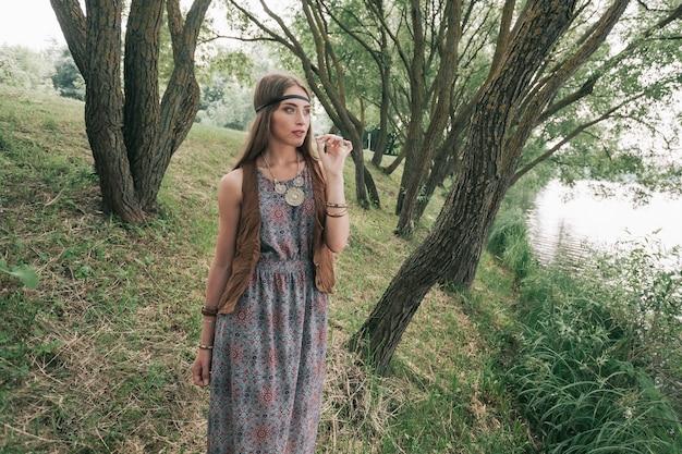 Schöne junge hippie-frau auf einem spaziergang im stadtpark